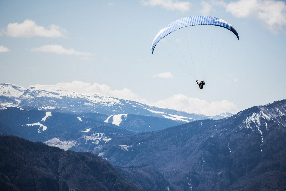 A hang glider flying over mountains to illustrated a blog post on hanging participles