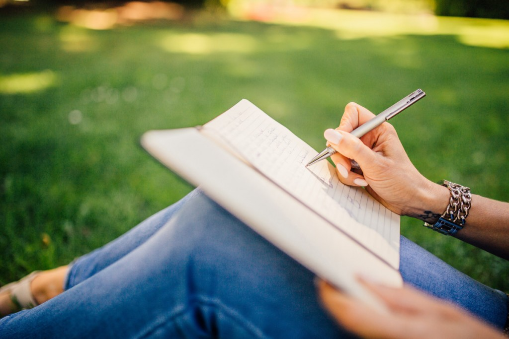 photograph of a woman writing in a notebook to illustrate a blog post on hyphenation