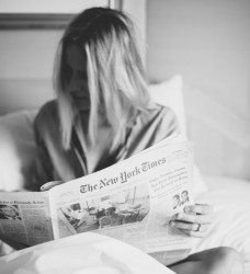 Woman reading a newspaper to illustrate a post on how to structure a news story