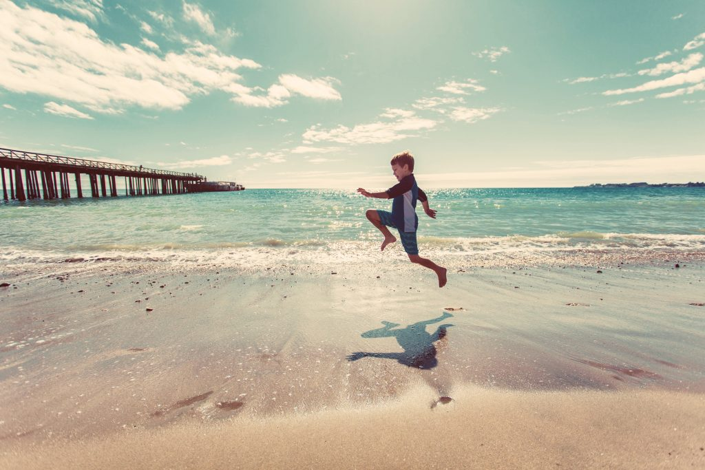 boy jumping on a beach to illustrate a post about relative pronounds