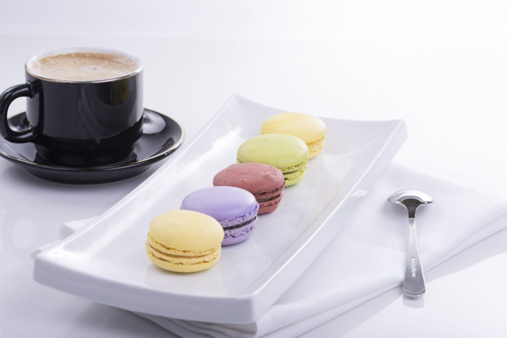 A photo of coffee and a row of macaroons to illustrate a blog post on 5 ways to keep your writing consistent
