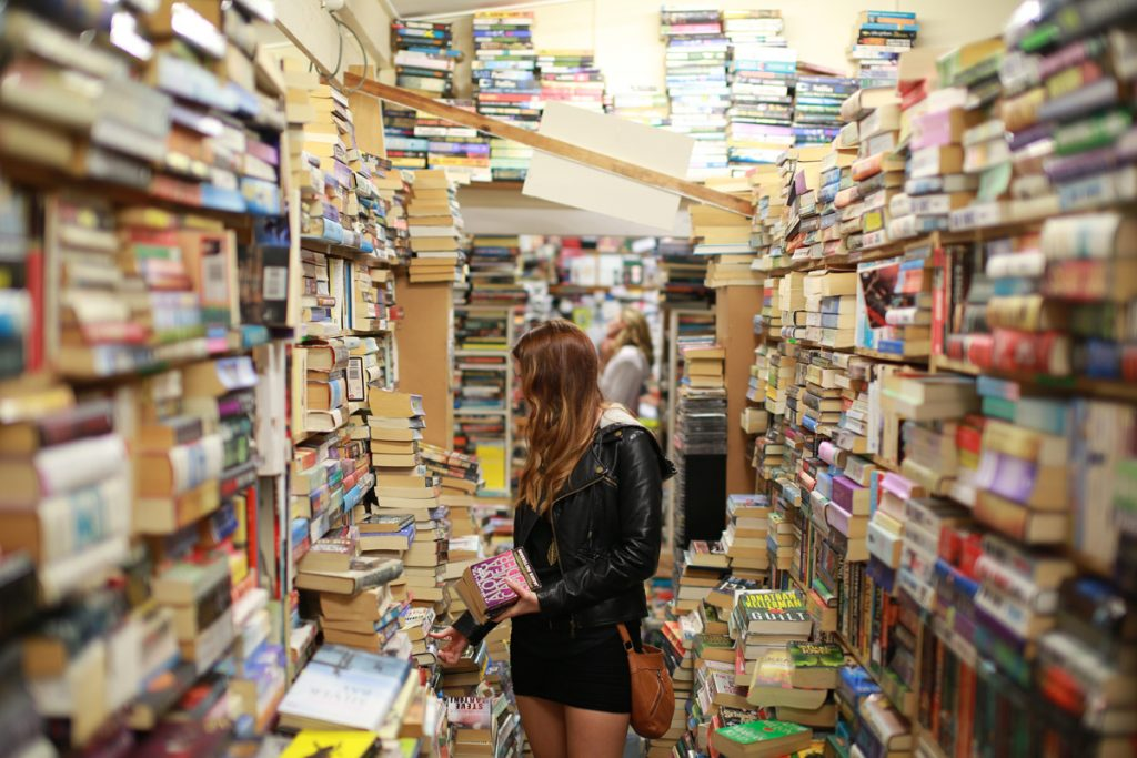 photo of girl in a bookshop to illustrate post on reading list